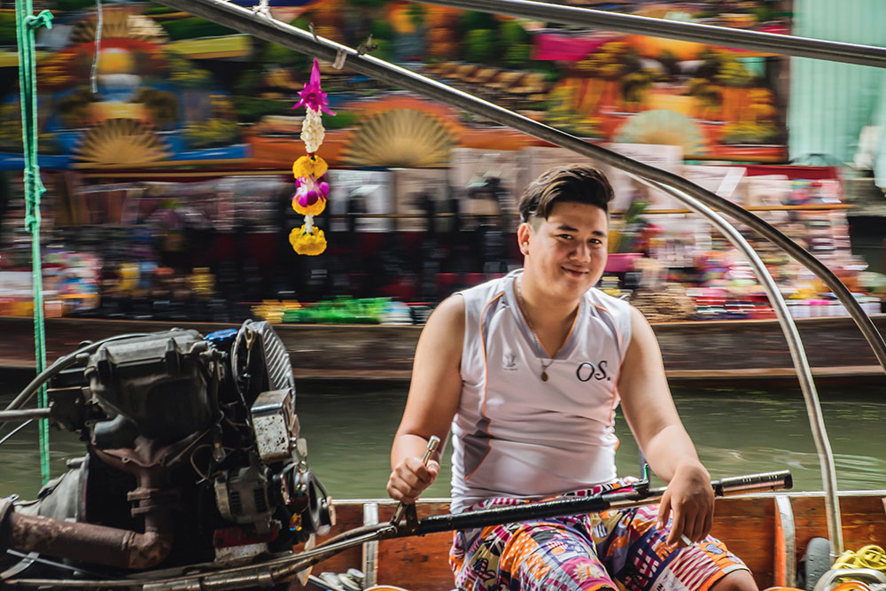 Damnoen Saduak floating market young man smiling Bangkok Thailand